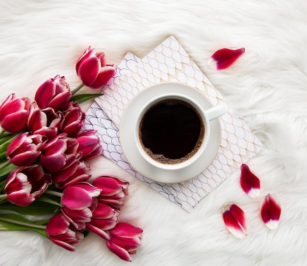 Taza de café y tulipanes rosados