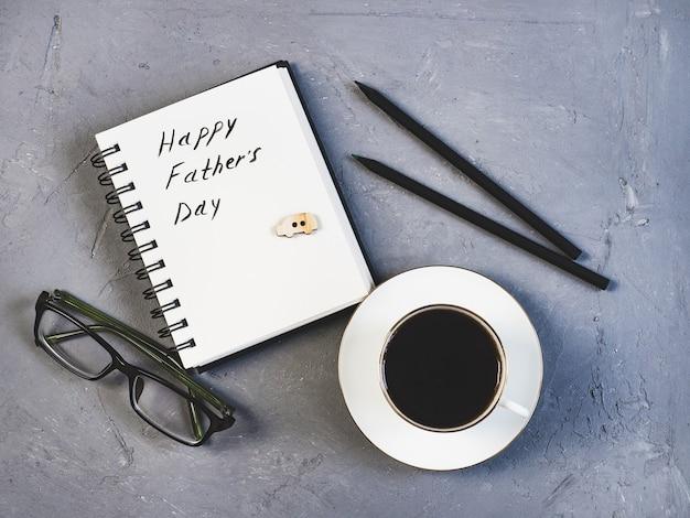Taza de café, vasos, bolígrafo y libreta.