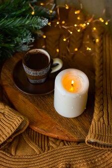 Una taza de café y una vela en una pizarra sobre un suéter cálido y acogedor y una ramita de un árbol de navidad