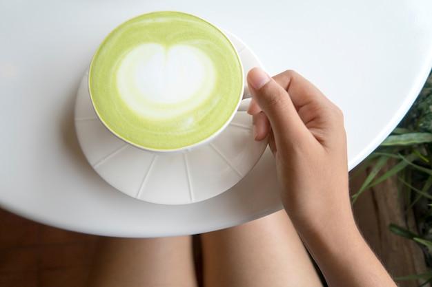 Taza de café verde con leche matcha en la mesa blanca. vista superior.