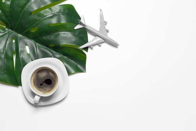 Taza de café vista superior y hoja de monstera