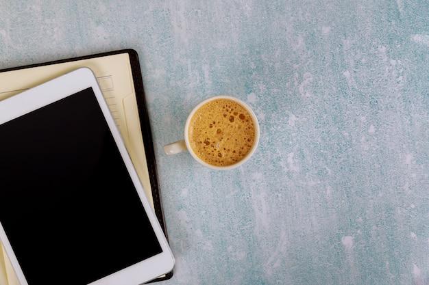 Taza de café con vista superior del lugar de trabajo y planificador semanal para negocios con lista de tareas pendientes en tableta digital