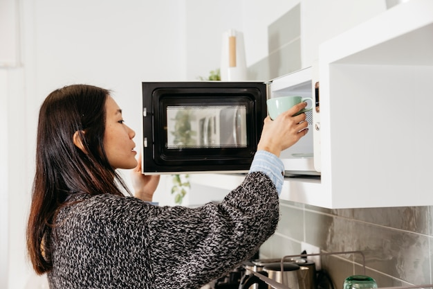 Taza de calentamiento de mujer con bebida en microondas