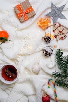 Taza caliente de té con las mandarinas y los suéteres en fondo de la cama con las luces. concepto de invierno acogedor.