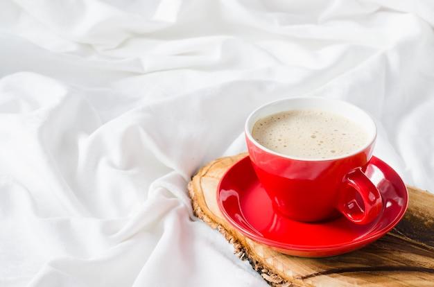 Taza de cappuccino caliente. desayuno en la cama.