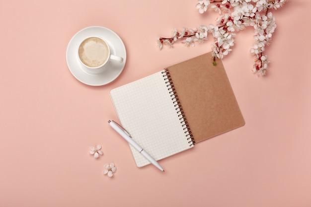 Una taza de capuchino blanco con flores de sakura, cuaderno, auriculares, bolígrafo.