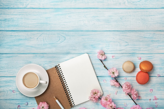 Taza de capuchino blanco con flores de sakura, cuaderno, macarons, en una mesa de madera azul