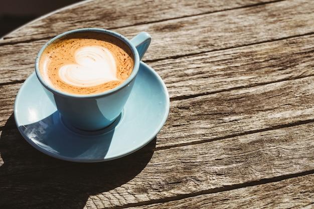 Taza de capuchino con café en la mesa de madera en la cafetería.