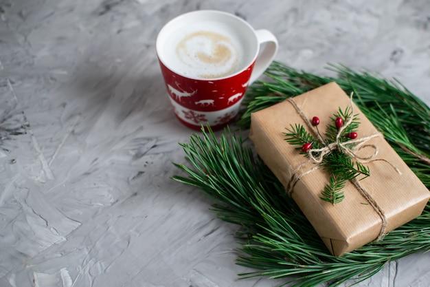 Taza con capuchino caja de regalo de navidad decoración decoración natural concepto de fiesta de año nuevo conos de pino vintage rama de abeto