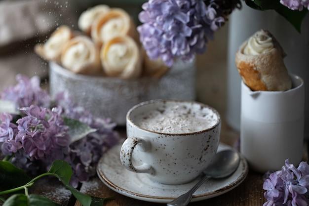 Taza de capuchino y conos de pastel de hojaldre con crema de vainilla en una caja de metal en primavera bodegón con un ramo de lilas en una mesa de madera