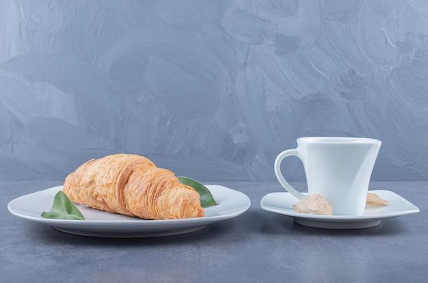 Taza de capuchino y croissant para desayunar sobre fondo gris.