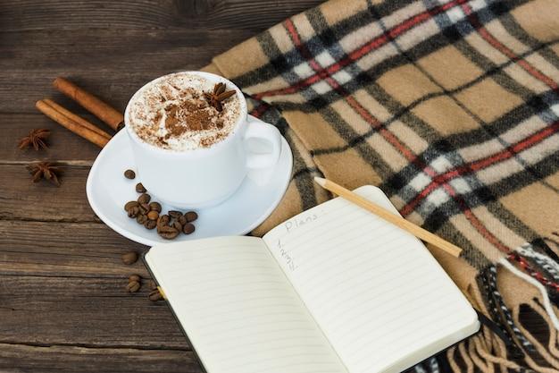 Taza de capuchino y cuaderno y cuadros a cuadros sobre una mesa de madera marrón