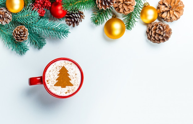 Taza de capuchino con forma del árbol de navidad en una tabla blanca.