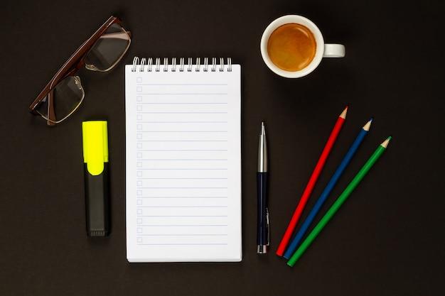 Una taza de capuchino, gafas, un marcador, bolígrafo, tres lápices de colores y un cuaderno para escribir. vista desde arriba.