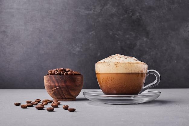 Una taza de capuchino con granos de café alrededor.