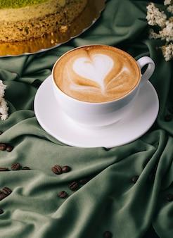 Taza de capuchino con granos de café y pastel sobre la mesa