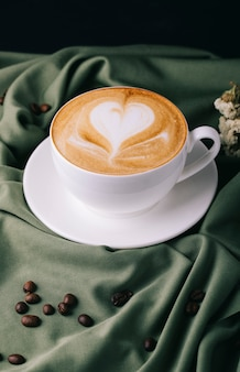 Taza de capuchino con granos de café sobre la mesa