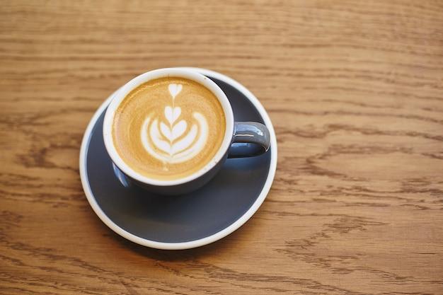 Taza de capuchino gris con arte latte en mesa de madera