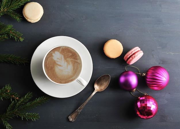 Taza de capuchino con pastel de macarrón, juguetes navideños