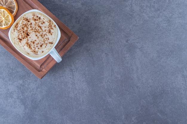 Una taza de capuchino en la placa de madera junto a rodajas de limón, sobre la mesa azul.