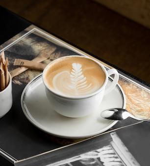 Taza de capuchino con rosetta latte art