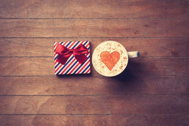 Taza de capuchino con símbolo de forma de corazón y caja de regalo sobre fondo de madera
