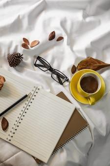 Taza de la carta de la libreta de café y un libro con una manta en una materia textil blanca en cama.
