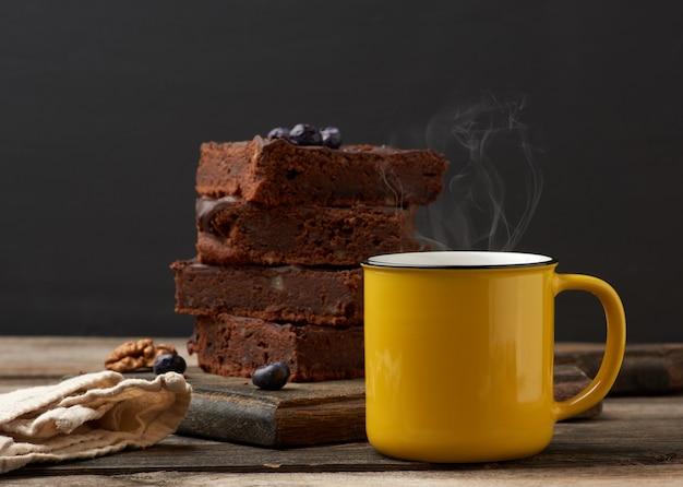 Taza de cerámica amarilla con café y una pila de trozos de brownie horneados