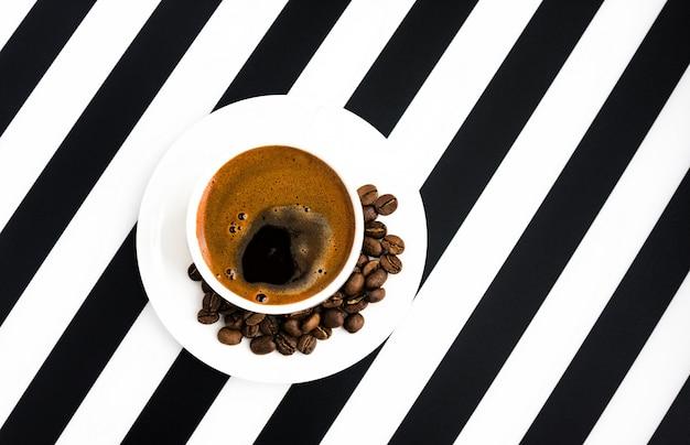 Taza de cerámica blanca de café fuerte sobre fondo de rayas