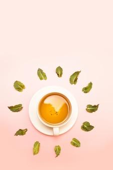 Taza de cerámica blanca con té de hierbas verde o negro con hojas de menta en rosa