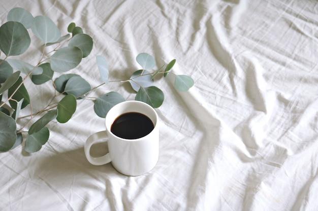 Taza de cerámica con café y hojas de chicle de plata