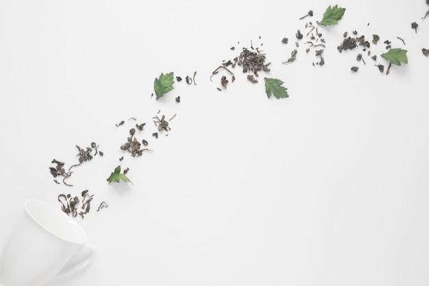Taza de cerámica con hierbas naturales aisladas sobre fondo blanco