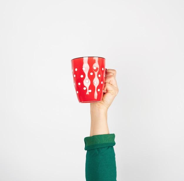 Taza de cerámica roja en una mano femenina en blanco