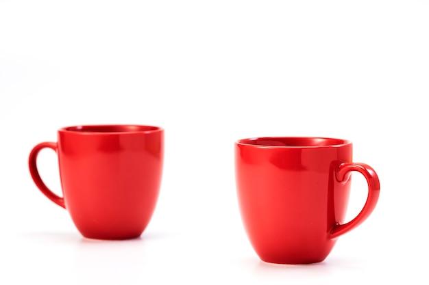 Taza de cerámica roja sobre fondo blanco.