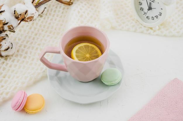 Taza de cerámica rosa con té de limón y macarrones sobre fondo blanco