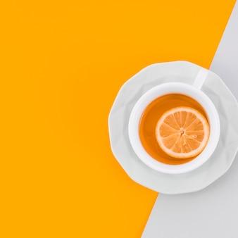 Taza de cerámica de té de jengibre con limón sobre fondo amarillo y blanco
