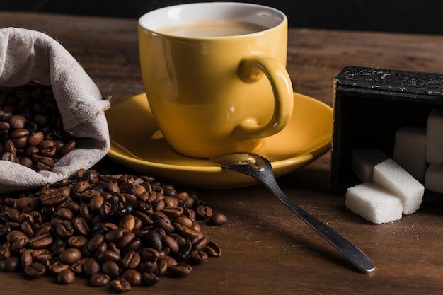 Taza cerca de azucarero y saco con granos de café.