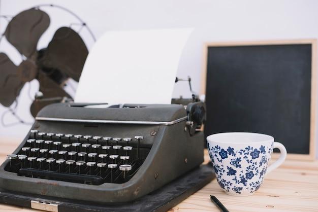 Taza cerca de la máquina de escribir retro