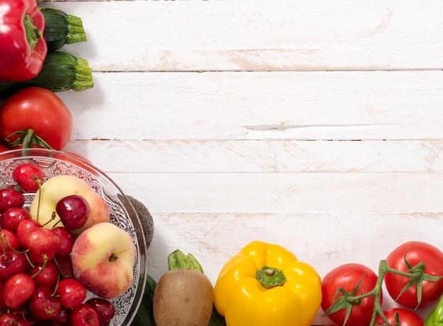 Taza de cerezas y duraznos con verduras