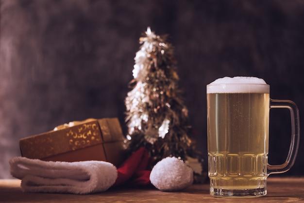 Taza de cerveza con decoraciones de navidad en la mesa de madera.