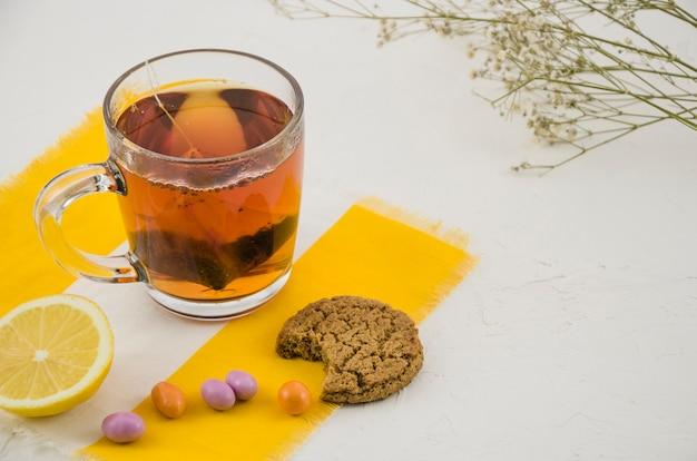 Taza china del té de hierbas con los caramelos y las galletas comidas en el fondo blanco con la ramita del gypsophila