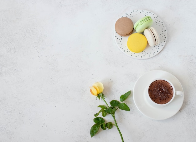 Taza de chocolate caliente con flores de macarons