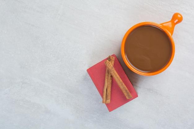 Taza de chocolate caliente, libro y canela sobre fondo gris. foto de alta calidad