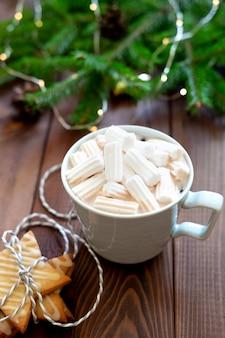 Taza de chocolate caliente con luces de navidad en segundo plano.