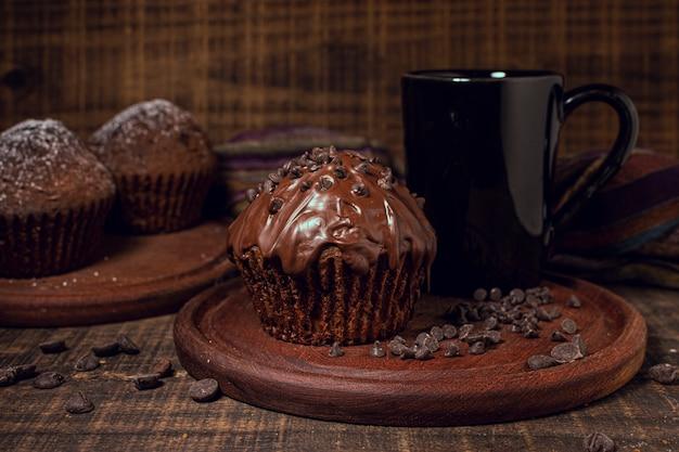 Taza de chocolate caliente y magdalenas dulces.