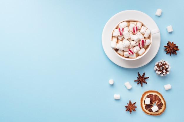 Taza de chocolate caliente con malvavisco en polvo de cacao y nueces de caramelo, naranjas sobre fondo azul pastel con espacio de copia. concepto de invierno de navidad