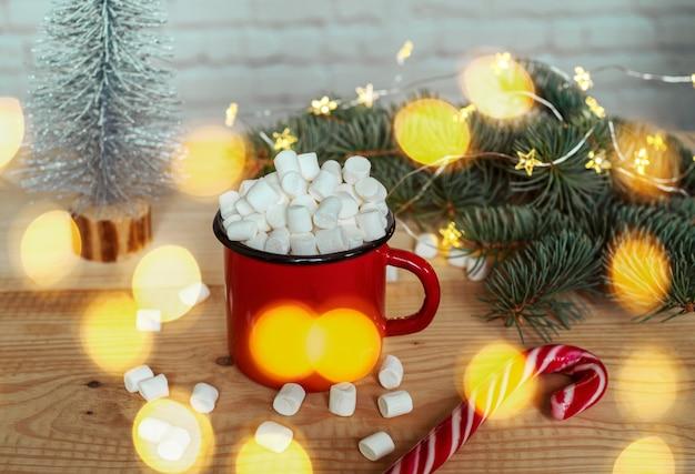Taza de chocolate caliente con malvaviscos con luces navideñas y ramas de árboles de navidad