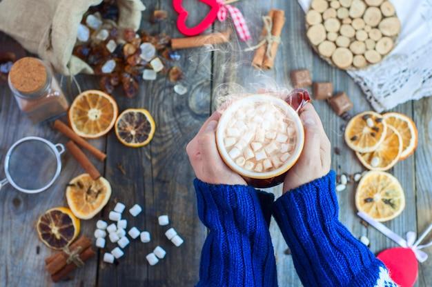 Taza de chocolate caliente con malvaviscos en manos humanas