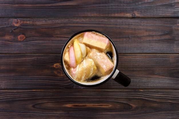 Taza con chocolate caliente y malvaviscos en mesa de madera. chocolate caliente con malvaviscos. cacao caliente con malvaviscos. taza de chocolate caliente con malvaviscos en la mesa de madera