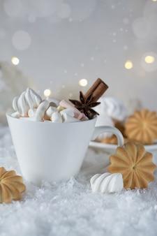 Una taza de chocolate caliente con malvaviscos o café con canela y galletas dulces en la nieve.